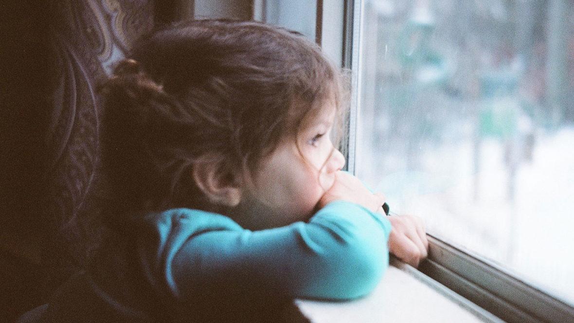 Kleines Mädchen ist krank und schaut aus dem Fenster