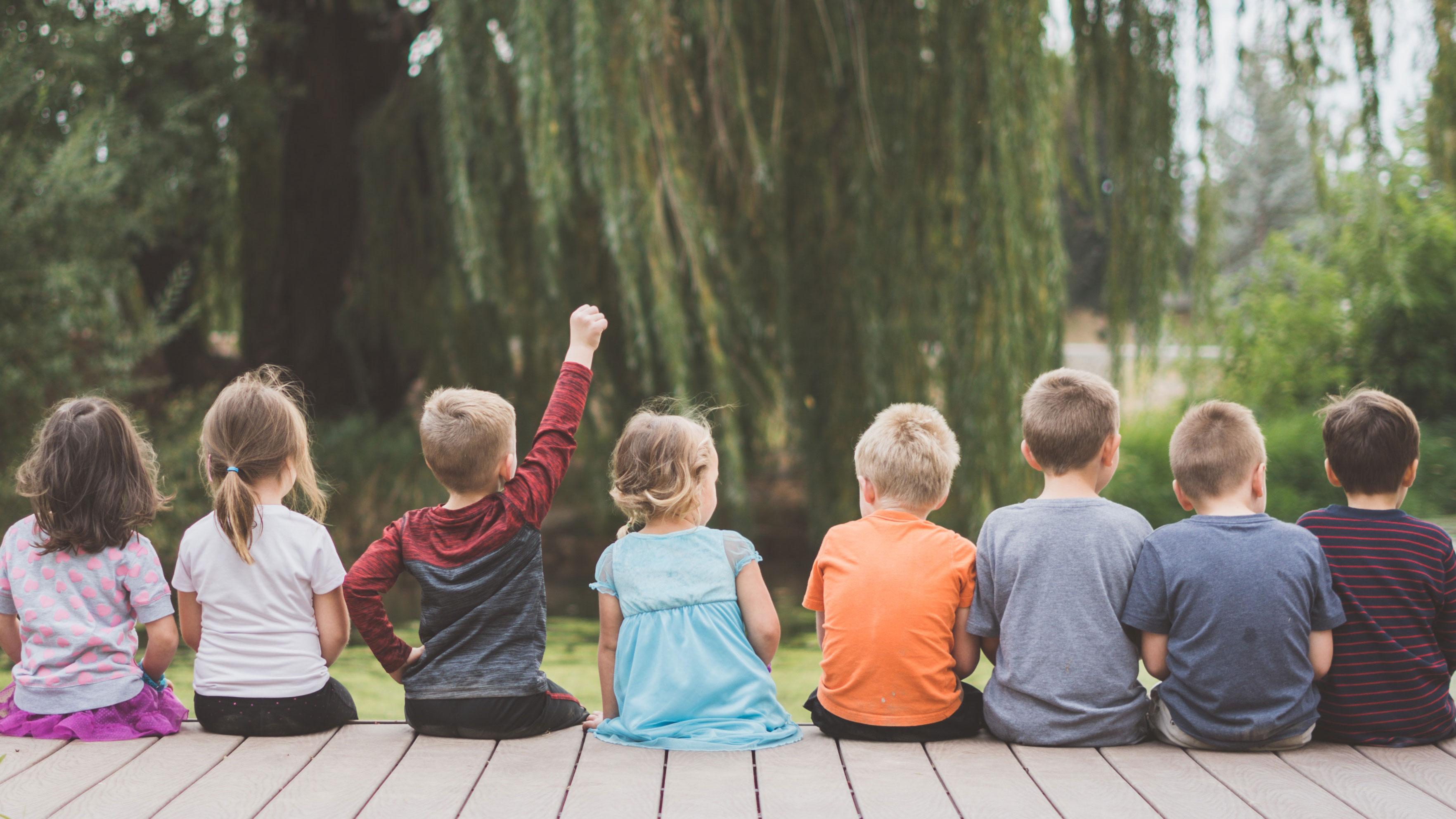 Kinder sitzen auf einem Steg
