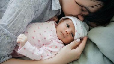 Mutter liegt mit Neugeborenem im Bett