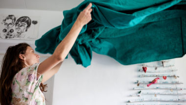 Frau schüttelt Decke auf