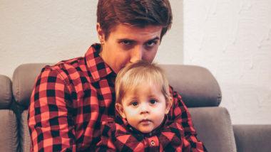 Vater und Sohn sitzen auf einem Sofa