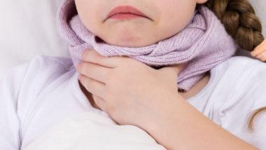 Kleines Mädchen mit Schal hält sich am Hals, weil sie Halsschmerzen hat.