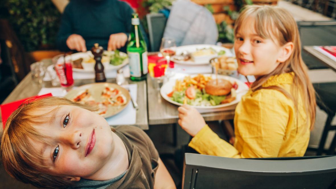Zwei Kinder die in einem Lokal sitzen und Essen.