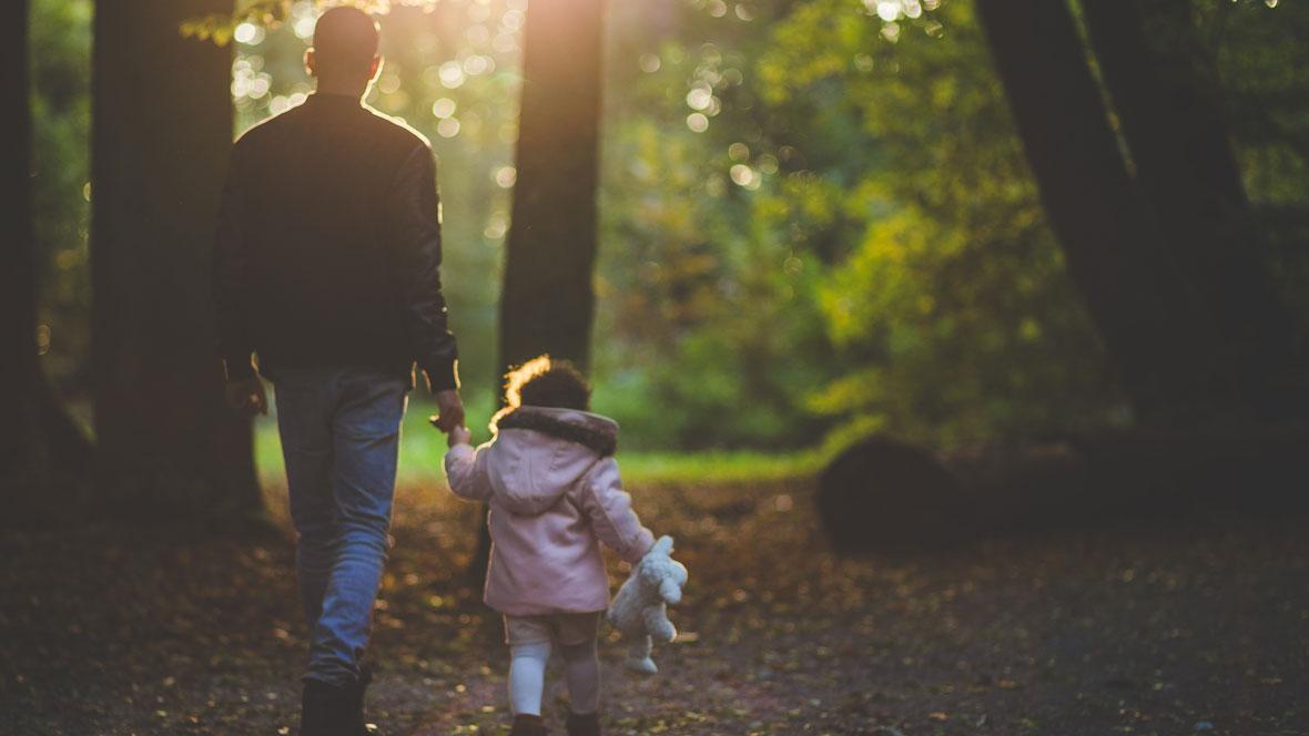 Vater geht mit Tochter im Wald spazieren