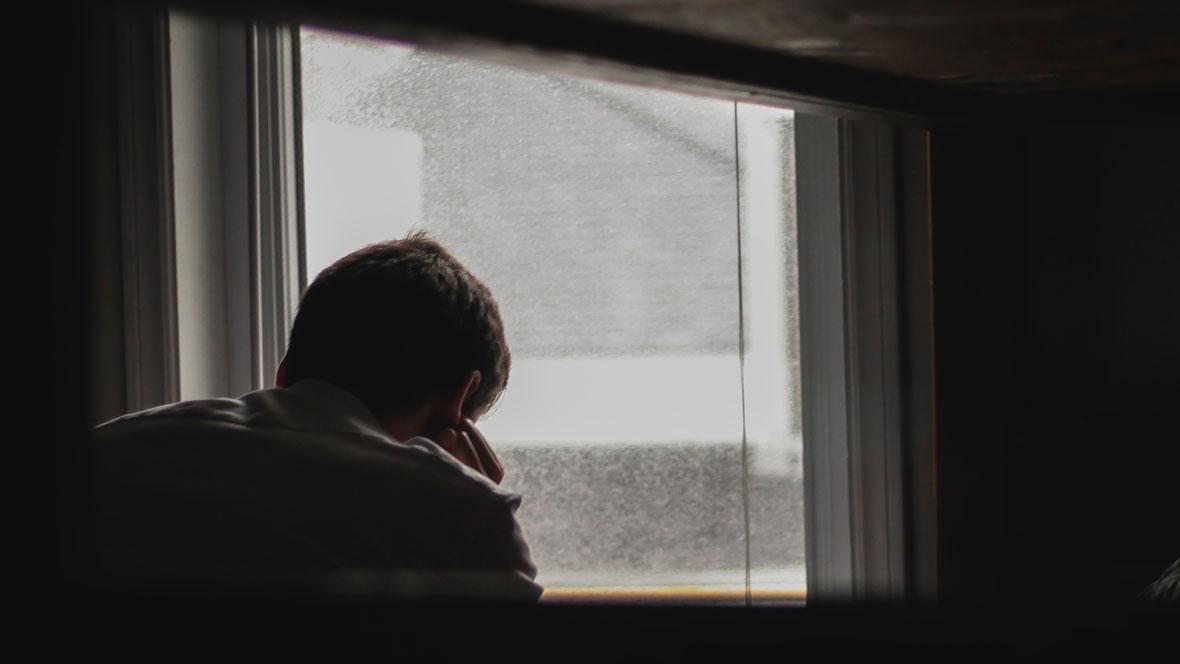 Mann sitzt am Fenster