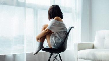 Frau sitzt auf einem Stuhl vor dem Fenster