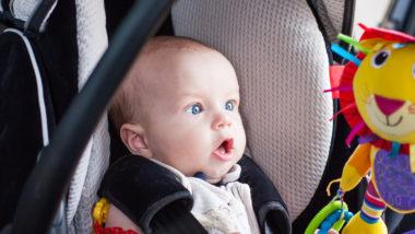 Baby sitzt in einem Kindersitz im Auto
