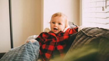 Kind steht auf einer Couch und lacht