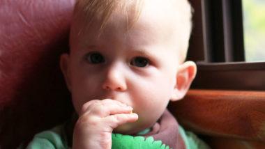 Kleines Junge steckt sich kleinen Gegenstand in den Mund