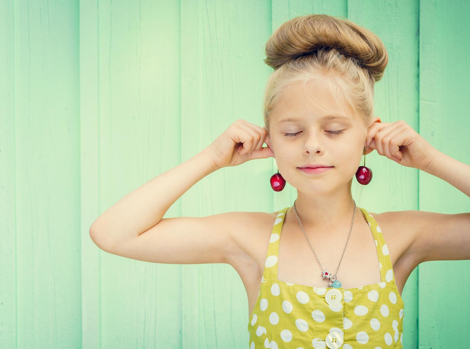 Mädchen hält sich Kirschen an die Ohren