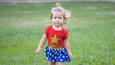 Mädchen mit Wonder Woman Shirt geht über Wiese