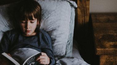 Junge liest im Bett