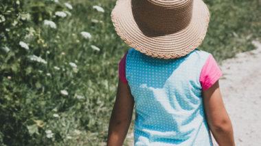 Kind mit Hut geht neben Wiese