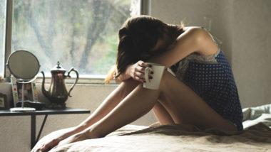 Traurige Frau sitzt auf einem Bett