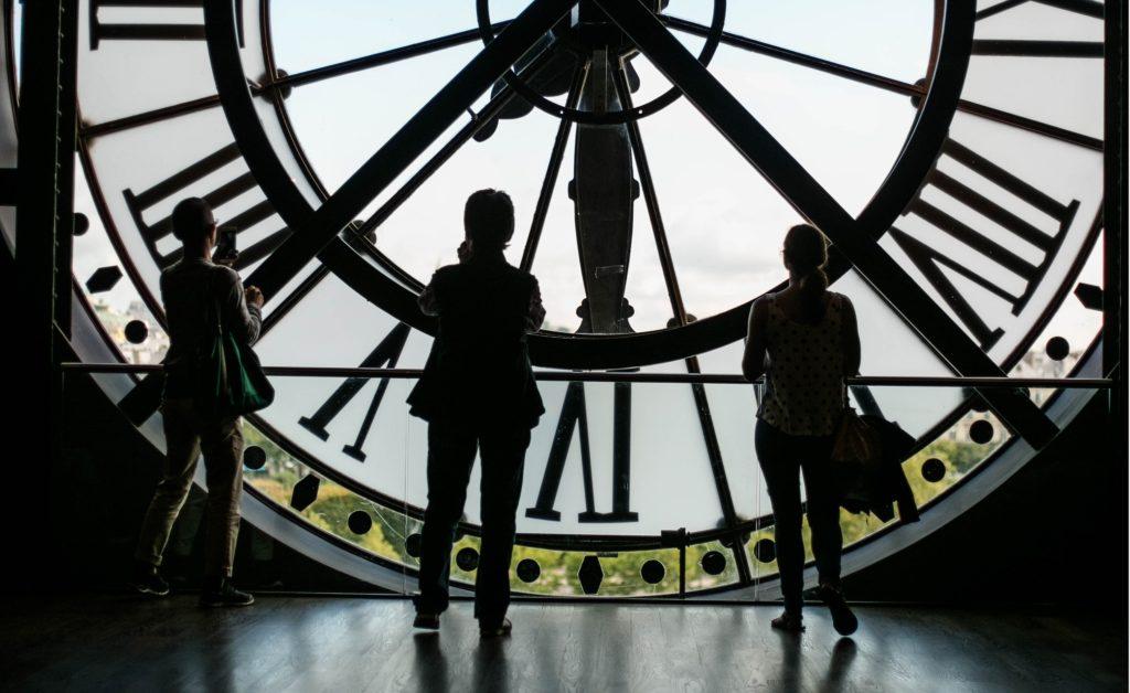drei Menschen die in einer riesen Uhr stehen und nach draußen schauen