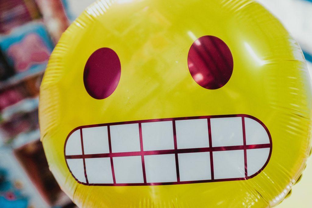 Ein grinsender Emoji-Luftballon.