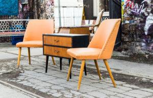 Zwei Stühle und einen Beistelltisch.