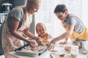 Eine Junge Mutter die mit ihren Kindern kocht.