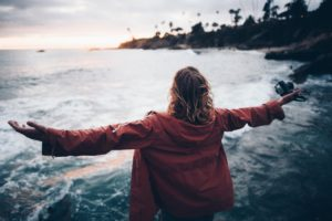 Mädchen steht mit ausgestreckten Armen am Strand.