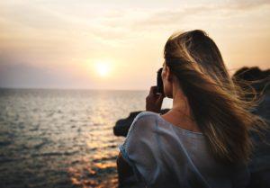 Frau die ein Foto vom Sonnenuntergang macht.