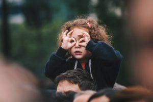 Kind sizt auf den Schultern des Vaters und formt eine Brille mit den Fingern.