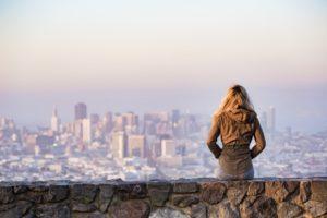 Frau sitz auf einer Mauer vor Stadtaussicht