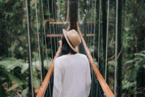 Frau mit Hut läuft auf Hängebrücke im Dschungel