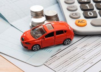 kuvassa pieni auto ja autolainasopimus ja autolainapaperit