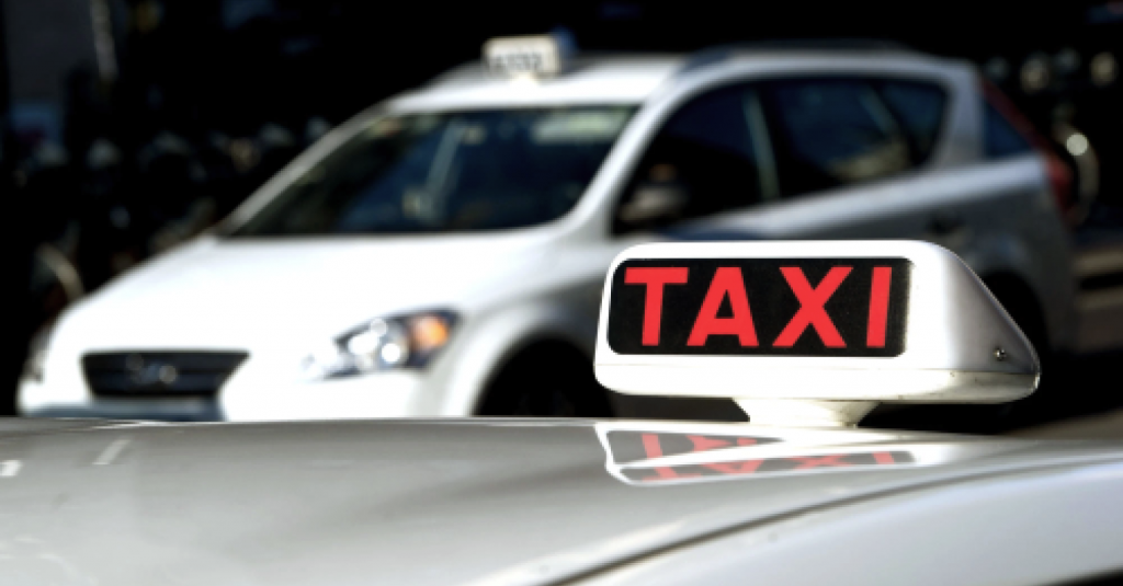 kuvassa taksi ja taksikyltti