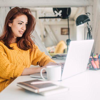 Frau mit Laptop sitzt in einem Loft