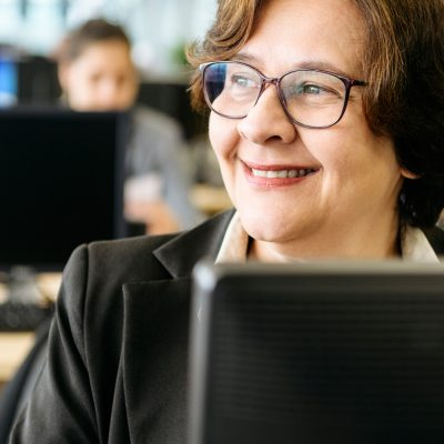 Eine Frau im Großraumbüro lächelt über ihren Bildschirm.