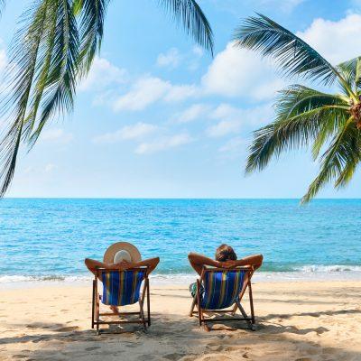 Strand mit Palmen und zwei Personen im Liegestuhl