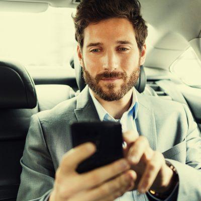 Geschäftsmann nutzt Smartphone im Taxi