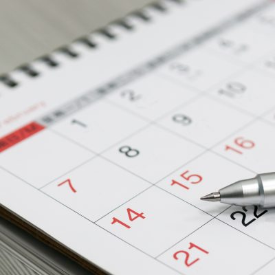 Kalender mit einem Stift darauf liegend
