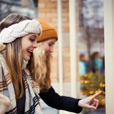 Junge Frauen schauen begeistert auf ein Schaufenster