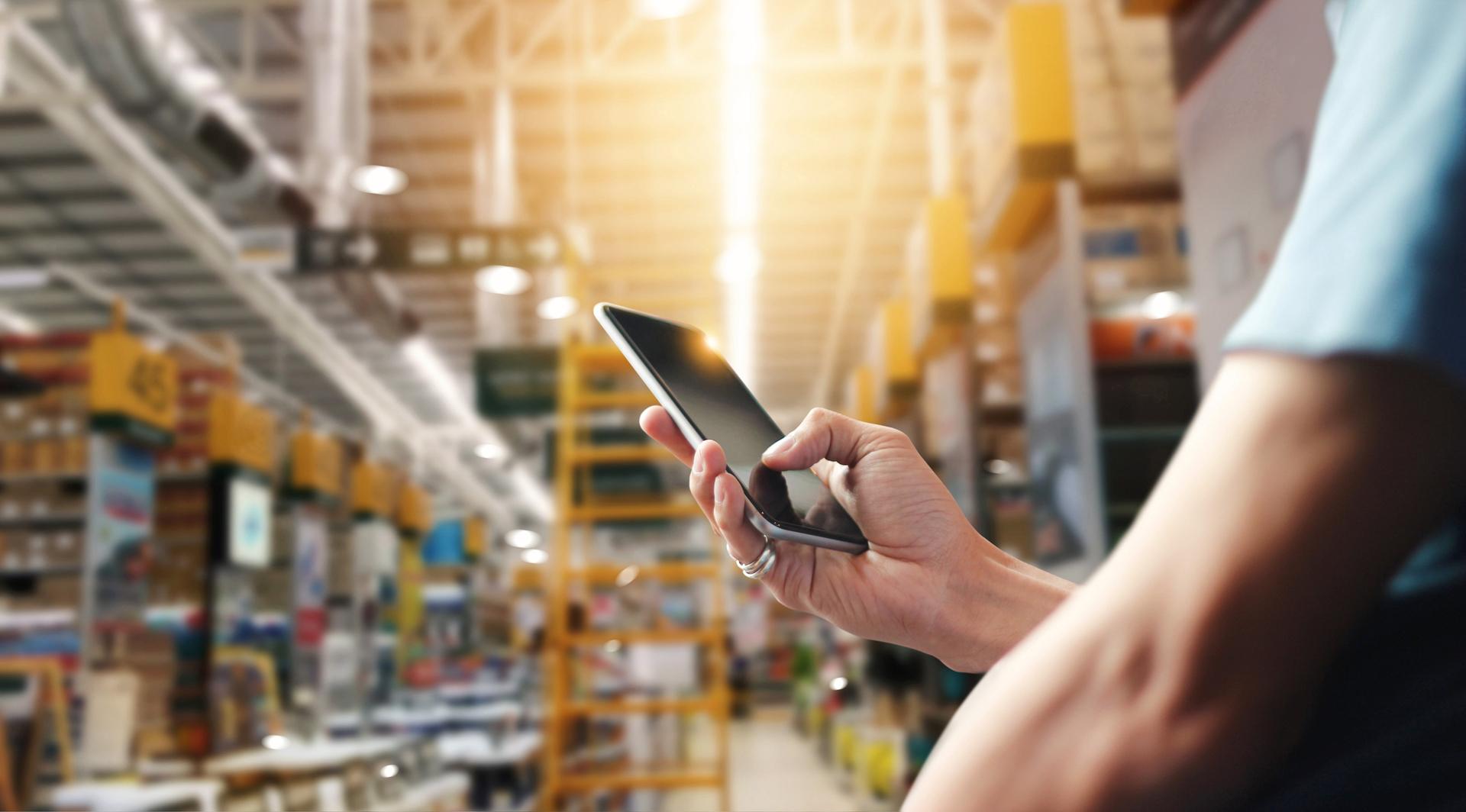 Logistik-Mitarbeiter prüft im Lagerhaus RFID-Transponder mit Smartphone