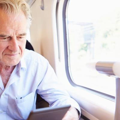 Älterer Mann sieht auf sein Tablet