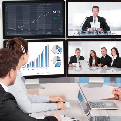 Vier Mitarbeiter sitzen an einem Tisch und verfolgen eine Videokonferenz auf vier Bildschirmen.