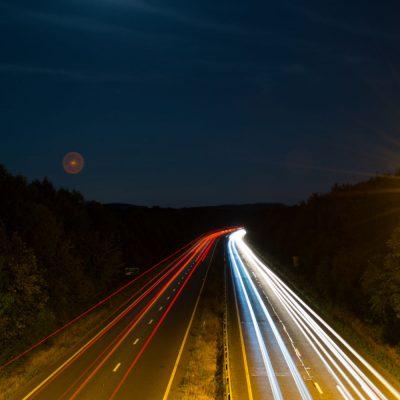 Foto einer Autobahn mit schnellen Autos bei Nacht