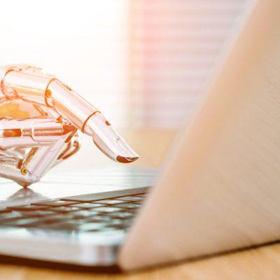 Eine Roboterhand bedient einen Laptop