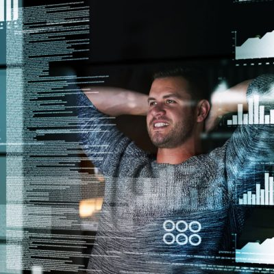 Ein junger Mann sitzt vor einem transparenten Screen mit Zahlen und Grafiken