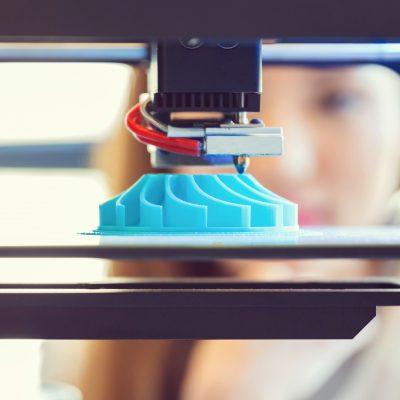 Junge Frau beobachtet einen 3D Druck.