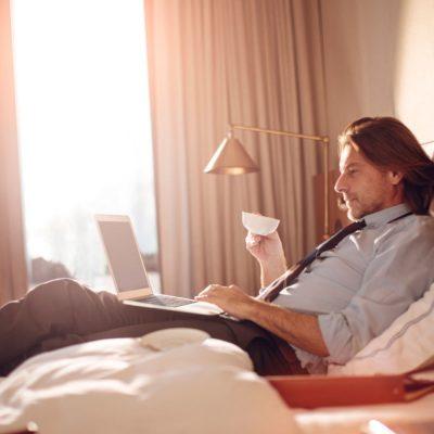 Mann, der auf einem Hotelbett sitzt