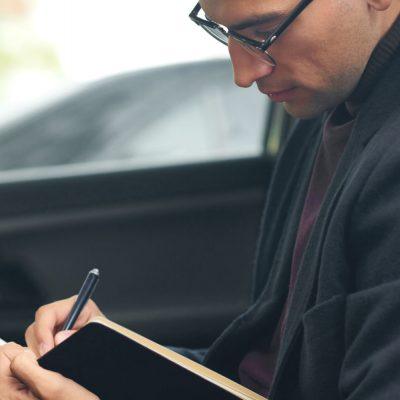 Ein Geschäftsmann trägt eine Fahrt in sein Dienstfahrtenbuch ein.