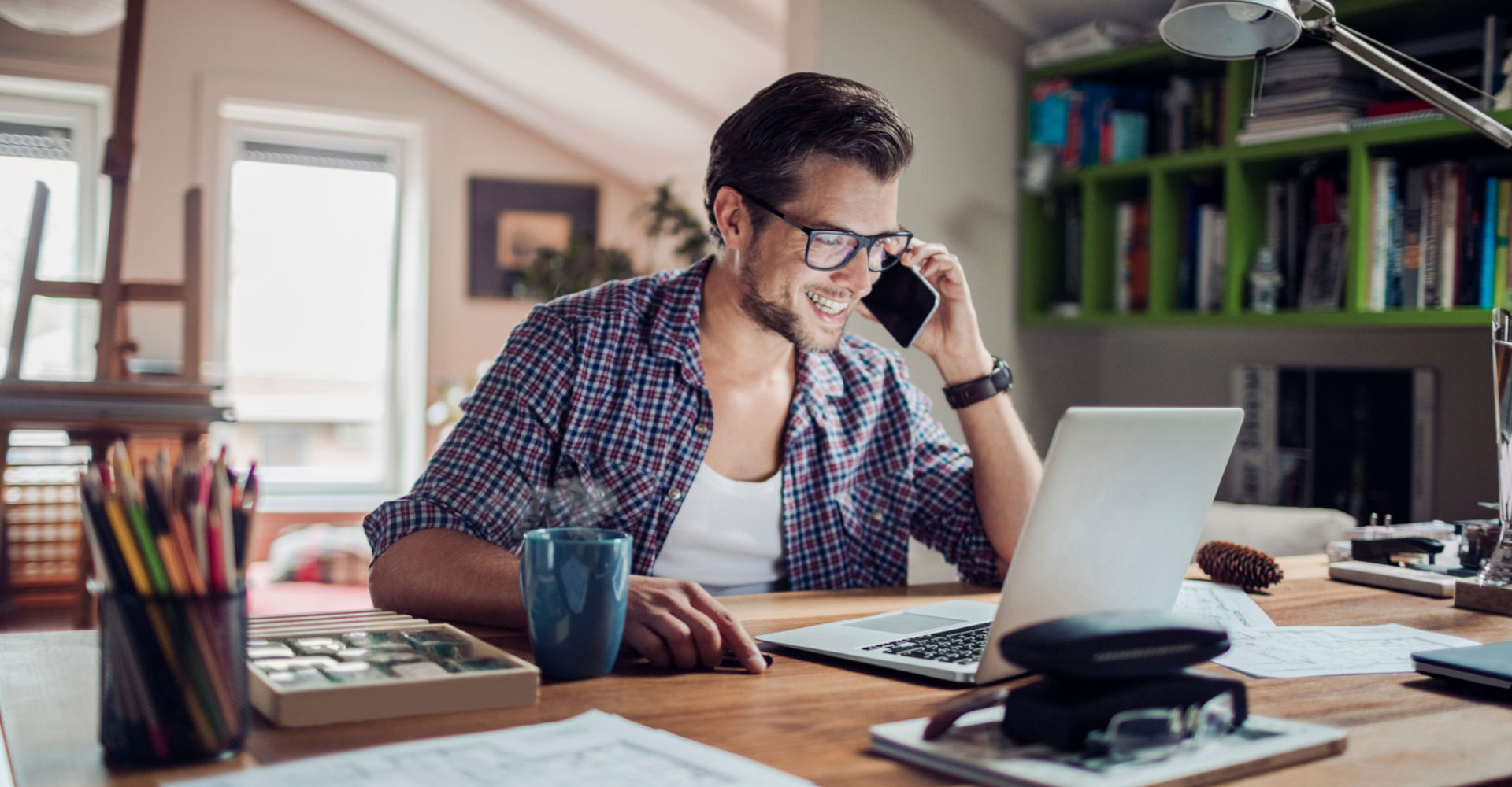 Junger Mann arbeitet und telefoniert im Homeoffice