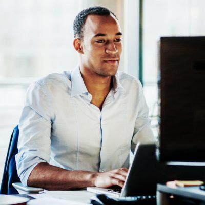 Junger Geschäftsmann nutzt eine feste IP-Adresse an seinem Büro-PC