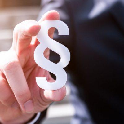 Symbolbild mit einem Geschäftsmann, der ein Paragraphensymbol festhält