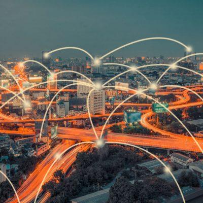 Eine Stadt mit Autobahnen wird durch IoT-Technologie symbolisch vernetzt.