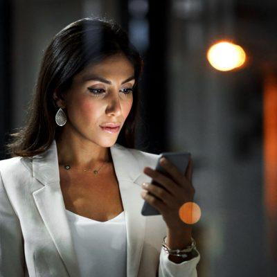 Junge Geschäftsfrau bedient ein Top-Smartphone