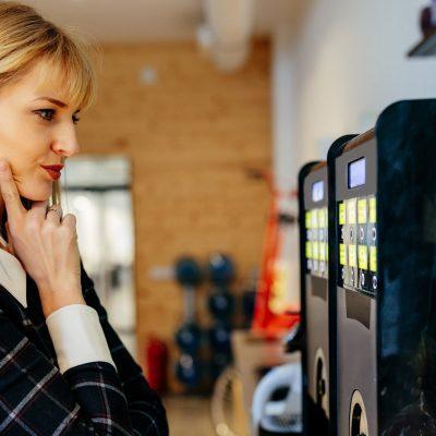 Geschäftsfrau bedient eine Pay-per-use-Kaffeemaschine mit IoT-Anbindung
